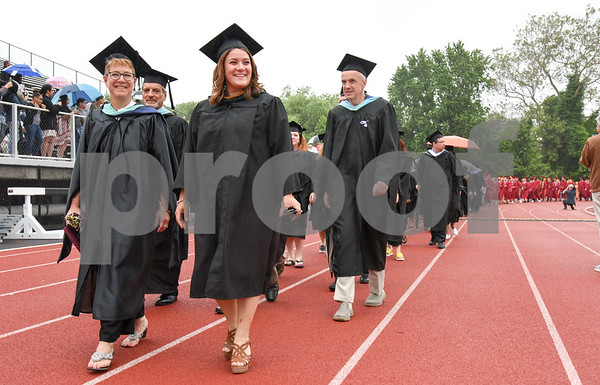 061617 Wesley Bunnell | Staff New Britain High School held graduation exercises on Friday afternoon outdoors at Veterans' Memorial Stadium despite intermittent rain showers. Superintendent of Schools Nancy Sarra, L, walks with Mayor Erin Stewart along with Principal NBHS Satellite Careers Academy Michael Foran.