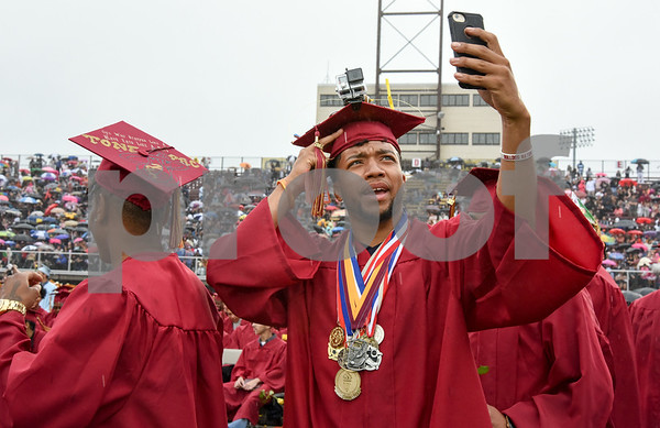 061617 Wesley Bunnell | Staff New Britain High School held graduation exercises on Friday afternoon outdoors at Veterans' Memorial Stadium despite intermittent rain showers. Donovan Dorce takes a selfie while wearing a video camera on his cap.