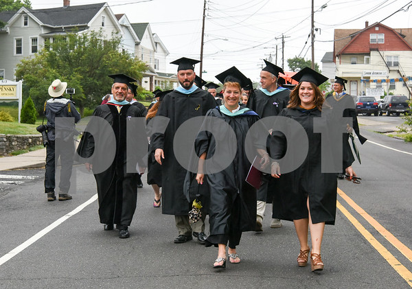 061617 Wesley Bunnell | Staff New Britain High School held graduation exercises on Friday afternoon outdoors at Veterans' Memorial Stadium despite intermittent rain showers. Paul Salina, L, Principal Joseph Pinchera, Superintendent of Schools Nancy Sarra & Mayor Erin Stewart lead the students down South Main St towards the stadium.