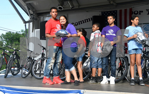 6/22/2017 Mike Orazzi | Staff Ashley Santos presents Pedro Lopez with a bike helmet and a free bike during the Bristol Boys & Girls Club Reach for the Stars event Thursday night.