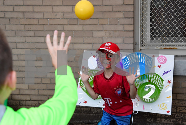 062317 Wesley Bunnell | Staff Michael Czyz, age 6, attempts to block a shot from his friend at the basket toss competition Friday evening at the Sacred Heart Festival.