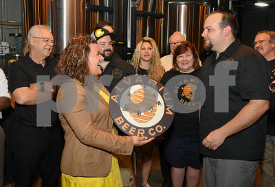 062317  Wesley Bunnell   Staff  Alvarium Beer Company held a ribbon cutting on Friday and became the first brewery open in New Britain since the mid 1950's.  Mayor Erin Stewart is presented with her own Alvarium Beer sign from Alvarium co-founder Mike Larson, R.