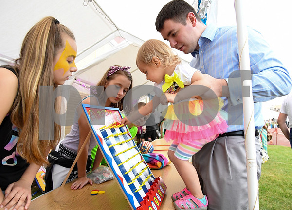 062317 Wesley Bunnell | Staff James Landon holds daughter Rosalie, age 21 months, as she plays the disk drop game at the Sacred Heart Festival on Friday evening.