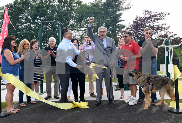 062917 Wesley Bunnell | Staff Newington Parks and Recreation staff and board members surround Mayor Roy Zartarian with his arm raised after helping to cut a ceremonial ribbon with Saputo plant manager Roque Lopez, L, celebrating the opening of the Saputo Fitness Center in Mill Pond Park on Thursday afternoon.