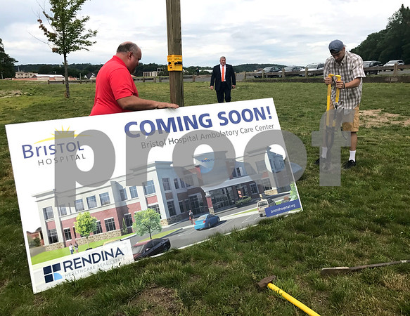 6/29/2017 Mike Orazzi | Staff Bristol Mayor Ken Cockayne arrives as Sign Sources' Mike McAdam and Sal D'Angelo install a sign at the corner of Riverside Avenue and Main Street in the area where Bristol Hospital is planning to build an ambulatory care center in downtown.