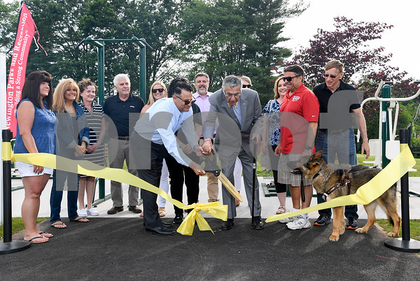 062917 Wesley Bunnell | Staff Newington Parks and Recreation staff and board members surround Saputo plant manager Roque Lopez, L, as he cuts the ribbon with Mayor Roy Zartarian celebrating the opening of the Saputo Fitness Center in Mill Pond Park on Thursday afternoon.