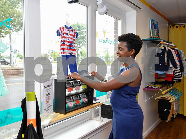 062917 Wesley Bunnell | Staff Owner of DribbleBabies Children's Clothing Davina Ismail changes the window display at her New Britain shop.