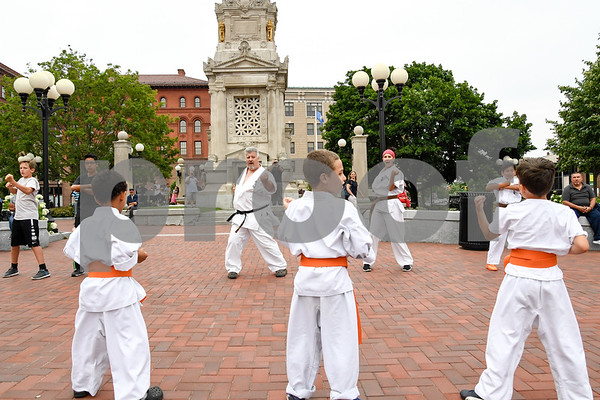 062917 Wesley Bunnell | Staff New Britain Judo and Karate School held an outdoor class in Central park on Thursday evening. City Hall can be seen in the background as Ethan Canales, L, Jacob Prokop and Isaac Dabkowski follow instructor Carl Messina, center.