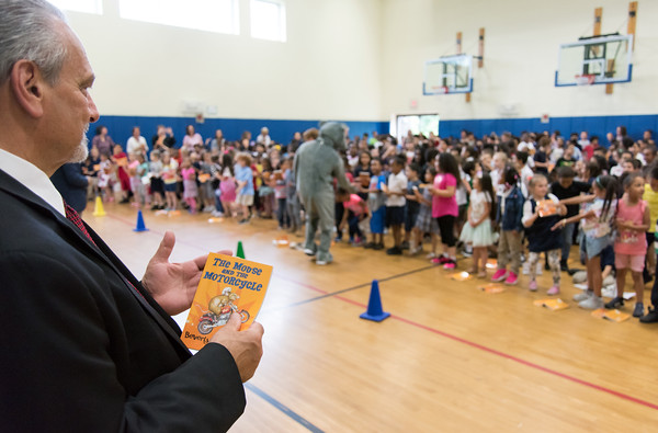 06/01/18 Wesley Bunnell | Staff CSDNB Chief Operating Officer Paul Salina holds a book as Lincoln Elementary School students are entertained by a mouse on Friday afternoon in the school gymnasium. The school held their One School, One Book event on Friday afternoon giving every student the same book, The Mouse on the Motorcycle, to bring home to be read with their parents. The books were wrapped with the title kept a secret until being passed out.