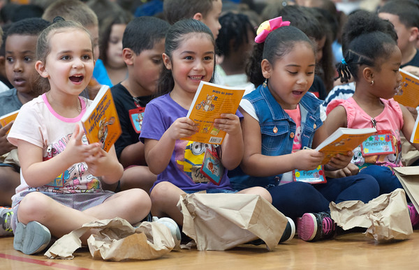 06/01/18 Wesley Bunnell | Staff Kindergarten students smile during Lincoln Elementary School's One School, One Book event on Friday afternoon. giving every student the same book, The Mouse on the Motorcycle, to bring home to be read with their parents. The books were wrapped with the title kept a secret until being passed out.