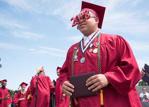 06/19/18 Wesley Bunnell | Staff A graduating New Britain High School senior wears 2018 glasses as he walks off stage after receiving his diploma during graduation exercises at Veterans' Memorial Stadium at Willow Brook Park on Tuesday morning.