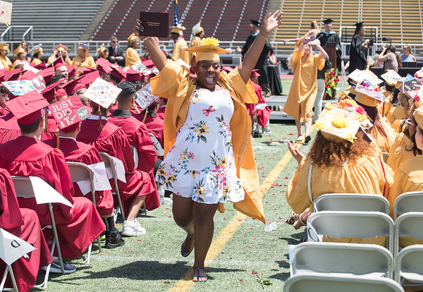 06/19/18 Wesley Bunnell | Staff A New Britain High School senior waves to the crowd as she runs down the aisle back to her seat after receiving her diploma during graduation exercises at Veterans' Memorial Stadium at Willow Brook Park on Tuesday morning.