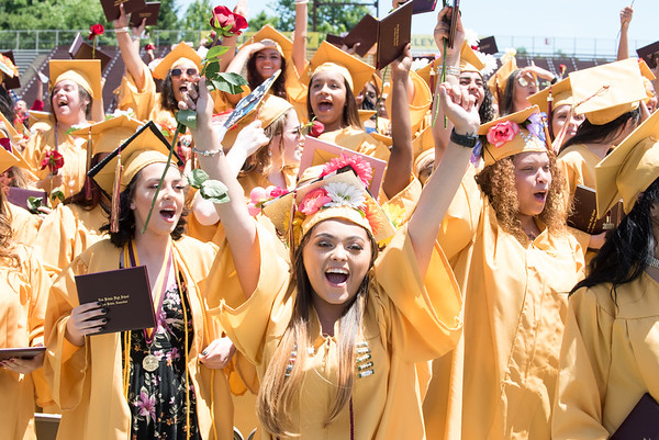 06/19/18 Wesley Bunnell | Staff New Britain High School seniors turn and scream toward the stands filled with family and friends at the conclusion of graduation exercises at Veterans' Memorial Stadium at Willow Brook Park on Tuesday morning.