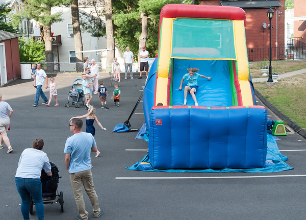 06/21/18 Wesley Bunnell | Staff Children slide down an inflatable slide on the first night of the Sacred Heart Parish Festival on Friday evening.