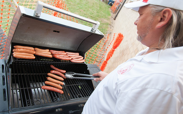 06/21/18 Wesley Bunnell | Staff Robert Wiecki cooks hot dogs and kelly dogs on the first night of the Sacred Heart Parish Festival on Friday evening.