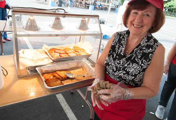 06/21/18 Wesley Bunnell | Staff Janina Brzoska works the potato pancake section on the first night of the Sacred Heart Parish Festival on Friday evening.