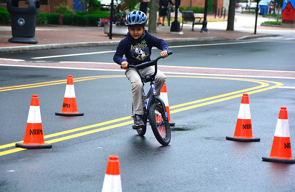 """6/23/2018 Mike Orazzi   Staff Iqbal Tanveer navigates traffic cones during the New Britain Police Department's Police Athletic League program, the Department of Parks and Recreation and the Department of Public Works' """"Bicycle Safety Day"""" event Saturday held in Central Park in downtown New Britain Saturday."""