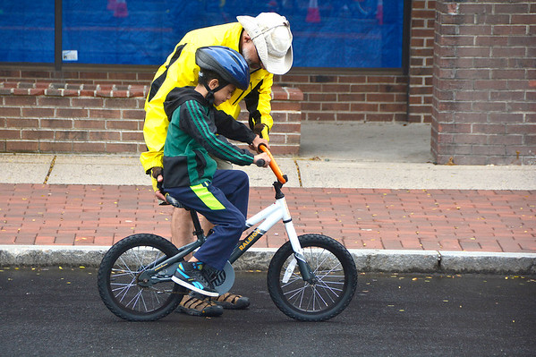 """6/23/2018 Mike Orazzi   Staff Steve Schiller assists Jace Pouncey during the New Britain Police Department's Police Athletic League program, the Department of Parks and Recreation and the Department of Public Works' """"Bicycle Safety Day"""" event Saturday held in Central Park in downtown New Britain Saturday."""