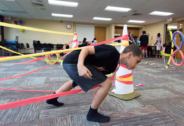 06/28/18 Wesley Bunnell | Staff Justin Bridge, age 9, climbs under the obstacle course of fire at the Tween Time Olympics at the New Britain Public Library on Thursday afternoon. The event is designed to bridge the gap from youth to teen events in the library.
