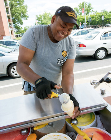 06/29/18 Wesley Bunnell | Staff Jose Nunez scoops ice cream and italian ice out of his cart on a hot Friday afternoon near New Brite Plaza. Jose walks around many parts of New Britain on days when its hot enough and not raining.