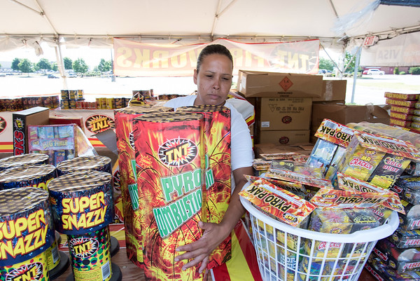 06/29/18 Wesley Bunnell | Staff The TNT Fireworks tent at 282 New Britain Ave in Plainville. New Britain resident and co-manager of the location Jessica Merced arranges a table of fireworks for sale on Friday afternoon in preparation for the weekend rush.