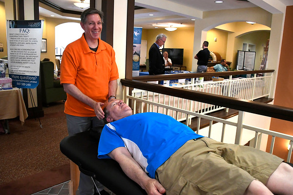 6/30/2018 Mike Orazzi | Staff An Infinite Abundance's Len Diana massages Robert Srulowitz during the Wise & Well Health Fair held at Atria in Farmington Saturday.
