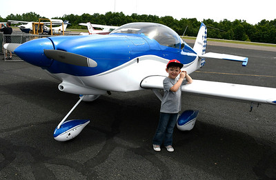 6/9/2018 Mike Orazzi | Staff Noah Churchelow stands next to plane on display during the 7th Annual Fly-In Car Show held at Robertson Airport in Plainville Saturday.