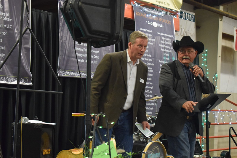 John Chapdelaine, director of the Eastern Colorado Community Fund, listens as auctioneer Jim Santomaso gets bids on an auction item so he can ring the triangle when the bidding reaches fair market value. 6.1.19 Sterling Community Fund Gala
