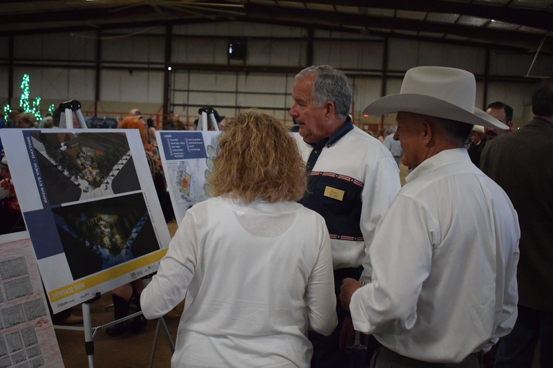 Sterling City Manager Don Saling (center) shows designs for a proposed urban park at the corner of Fourth and Main in downtown Sterling during the Sterling Community Fund Gala June 1, 2019.