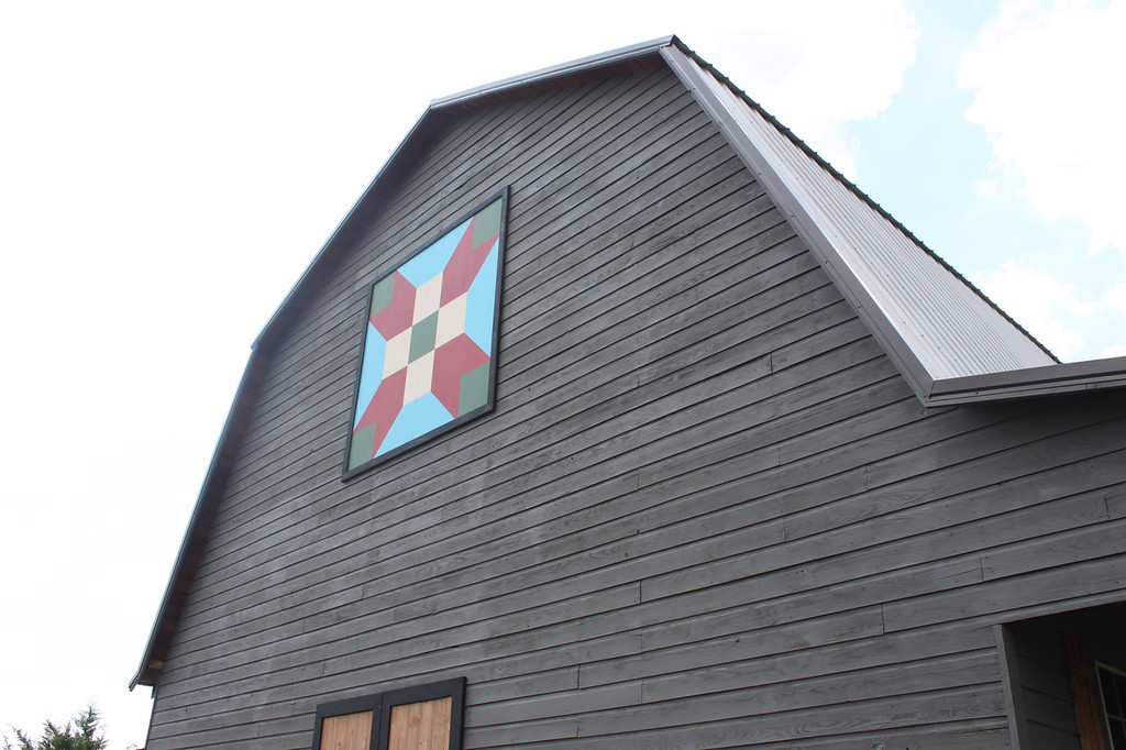 A black barn has a quilt patter in the middle