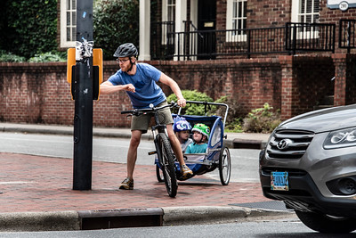 Pulling his kids in a bicycle buggy, this dad safely activated the crossing signal by using his elbow. (Bill Giduz photo)