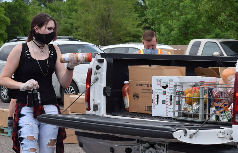 Volunteer Kelly Cisneros loads items into a truck during a mass food giveaway hosted by the Vineyard Church and The Pantry of Fremont on Friday. Carie Canterbury/Daily Record 5-29-20
