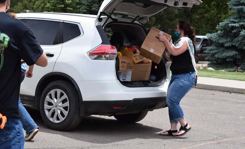 Volunteer Amanda Allen loads food into a vehicle during a mass food giveaway hosted by the Vineyard Church and The Pantry of Fremont on Friday. Carie Canterbury/Daily Record 5-29-20