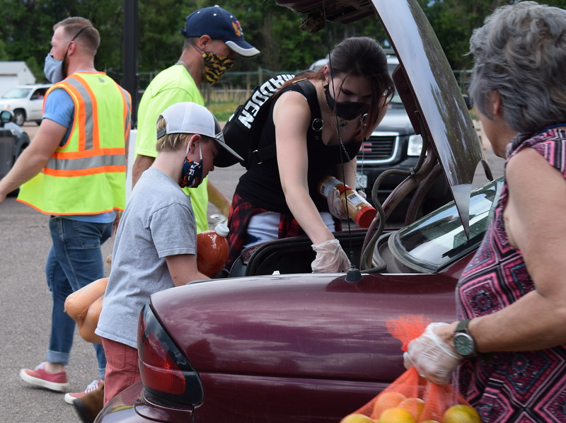 Volunteers load food into the trunk of a car during a mass food giveaway hosted by the Vineyard Church and The Pantry of Fremont on Friday. Carie Canterbury/Daily Record 5-29-20