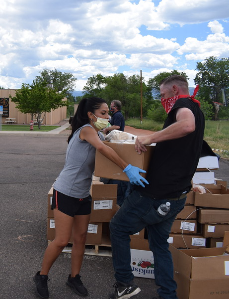 Volunteers Joetta Bender and Kyle Herrera load boxes of frozen meats during a mass food giveaway hosted by the Vineyard Church and The Pantry of Fremont on Friday. Carie Canterbury/Daily Record 5-29-20