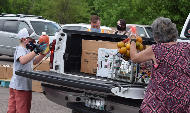 Leland Canady, 9, and other volunteers load items into a truck during a mass food giveaway hosted by the Vineyard Church and The Pantry of Fremont on Friday. Carie Canterbury/Daily Record 5-29-20