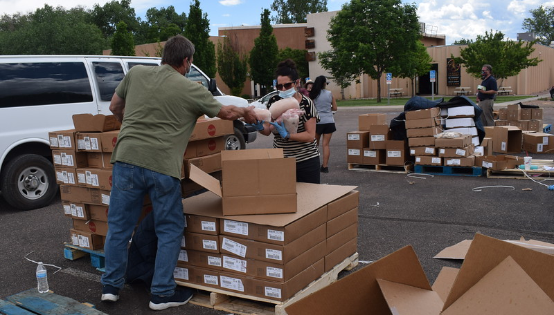 Volunteers distribute food during a mass food giveaway hosted by the Vineyard Church and The Pantry of Fremont on Friday. Carie Canterbury/Daily Record 5-29-20