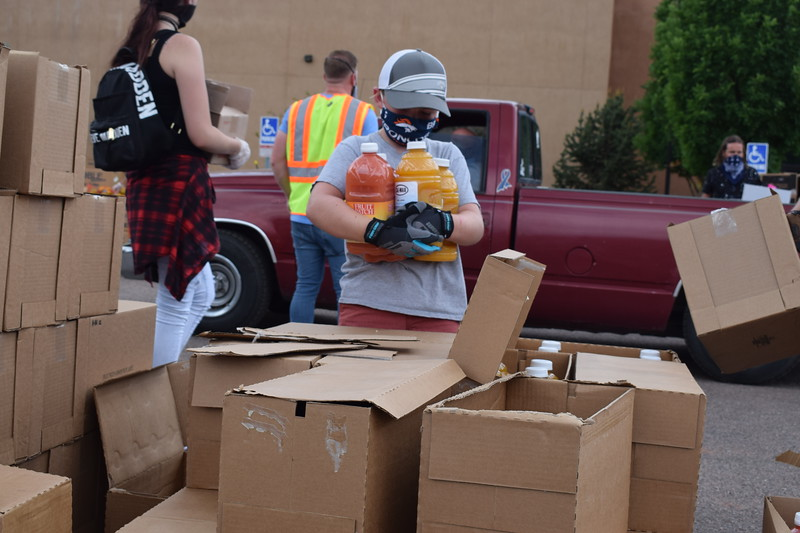 Leland Canady, 9, hands out bottles of juice during a mass food giveaway hosted by the Vineyard Church and The Pantry of Fremont on Friday. Carie Canterbury/Daily Record 5-29-20