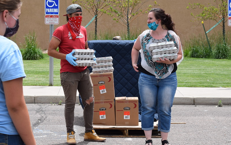 Volunteers Daren Miller and Amanda Allen hand out eggs during a mass food giveaway hosted by the Vineyard Church and The Pantry of Fremont on Friday. Carie Canterbury/Daily Record 5-29-20