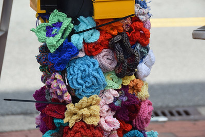 Each of the handmade knitted flowers was afixed to plastic netting, and the netting wrapped around a pole at the Main Street crosswalk.