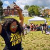 Karonika Brown, of the Lowell Litter Krewe team, celebrates a point as her teammate, Lowell Litter Krewe founder Brad Buitenhuys, picks up bags for another round in the background at a Toss Against Hate cornhole tournament on Lowell's South Common Sunday. The event was organized by the EAST Movement, which teamed up with the Lowell Litter Krewe to clean the South Common in the days before the fundraiser and community event. SUN/Robert Mills