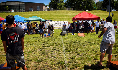 A 'Stop Asian Hate' banner catches the wind during a Toss Against Hate cornhole tournament on Lowell's South Common Sunday. The event was organized by the EAST Movement, a new organization that is trying to build community to stand against all forms of hatred in the wake of recent acts of violence against Asians nationwide. . SUN/Robert Mills SUN/Robert Mills