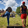 Karonika Brown, of the Lowell Litter Krewe team, tosses a bag as Sam Hy, of the Seasia team, prepares at a Toss Against Hate cornhole tournament on Lowell's South Common Sunday. The event was organized by the EAST Movement, which teamed up with the Lowell Litter Krewe to clean the South Common in the days before the fundraiser and community event. SUN/Robert Mills