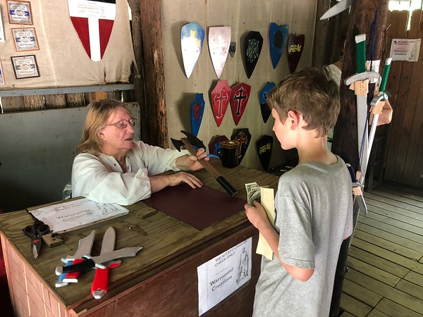 CHESLEY OXENDINE/Muskogee Phoenix<br /> Braden Surber purchases a wooden axe from Warmaster Creations during the Muskogee Renaissance Festival.