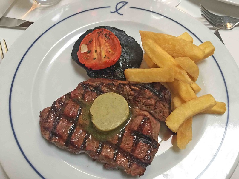 Grilled Longhorn Ribeye with Tripe-Cooked Chips, Roasted Tomato, Field Mushroom, Garlic & Parsley Butter