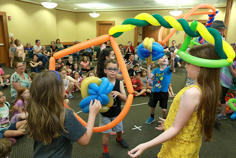 Jungle Jim performed his balloon and magic show at the Leominster Public Library on Wednesday afternoon. During Jim's show kids got to participate in many ways. Here Maddy Linstruth, 9 on right, from Leominster wears some balloons as a basketball net while Caleb Miranda, 6, from Leominster and Sarah Joseph, 8, from Berlin shoot a balloon ball through her hoop during the show.SENTINEL & ENTERPRISE/JOHN LOVE
