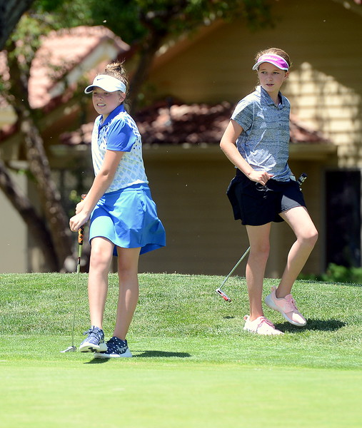 Reece Bandemer kicks her leg as her putt rolls past the hole with Ellie Barry looking on during the Junior Optimist golf tournament Monday at the Olde Course in Loveland. (Mike Brohard/Loveland Reporter-Herald)