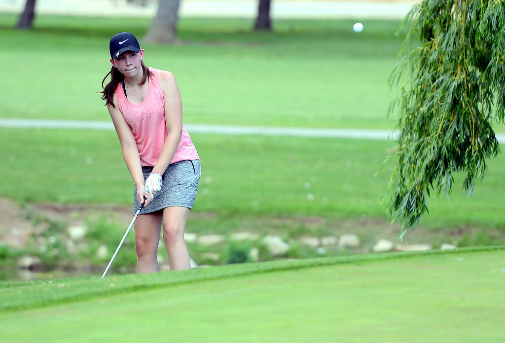 . Rylee Collins chips onto the fifth green during the Junior Optimist golf tournament Monday at the Olde Course in Loveland. (Mike Brohard/Loveland Reporter-Herald)