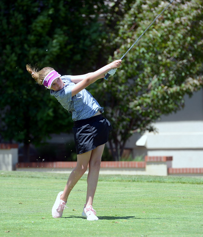 . Ellie Barry goes with an iron off the tee during the Junior Optimist golf tournament Monday at the Olde Course in Loveland. (Mike Brohard/Loveland Reporter-Herald)