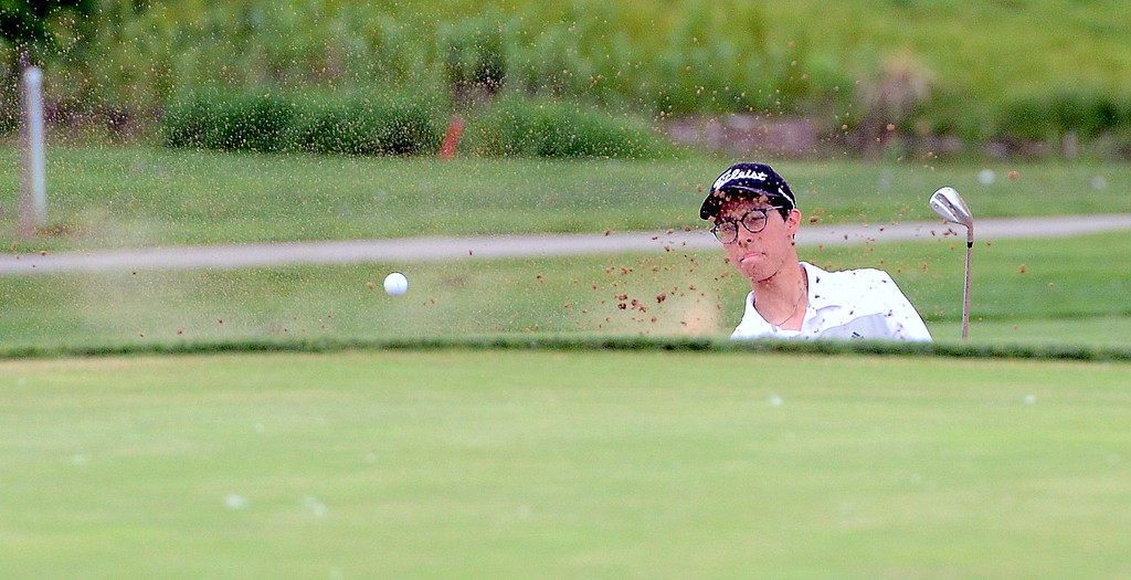 . Micah Ramirez hits out of a green-side bunker on No. 18 during the Junior Optimist golf tournament Monday at the Olde Course in Loveland. (Mike Brohard/Loveland Reporter-Herald)